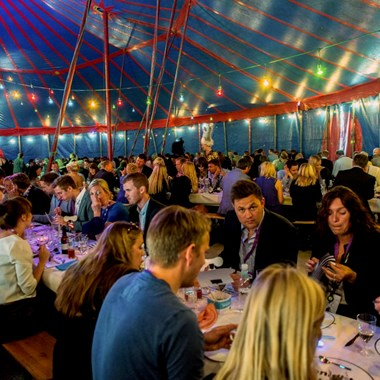 people eating dinner in circus-tent